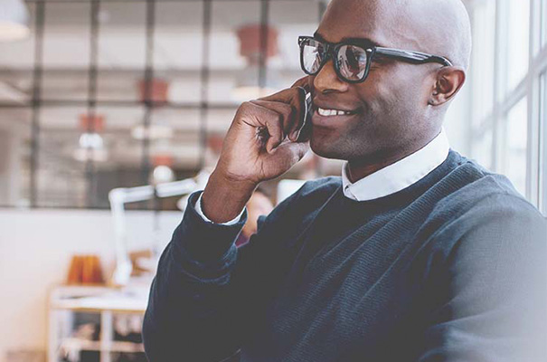 An African American business man with glasses is talking on a phone and smiling